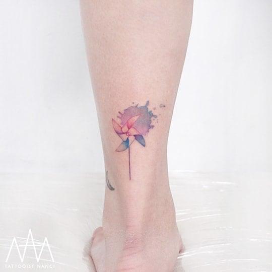 Watercolor Pinwheel Tattoo on Leg by Tattooist Nanci