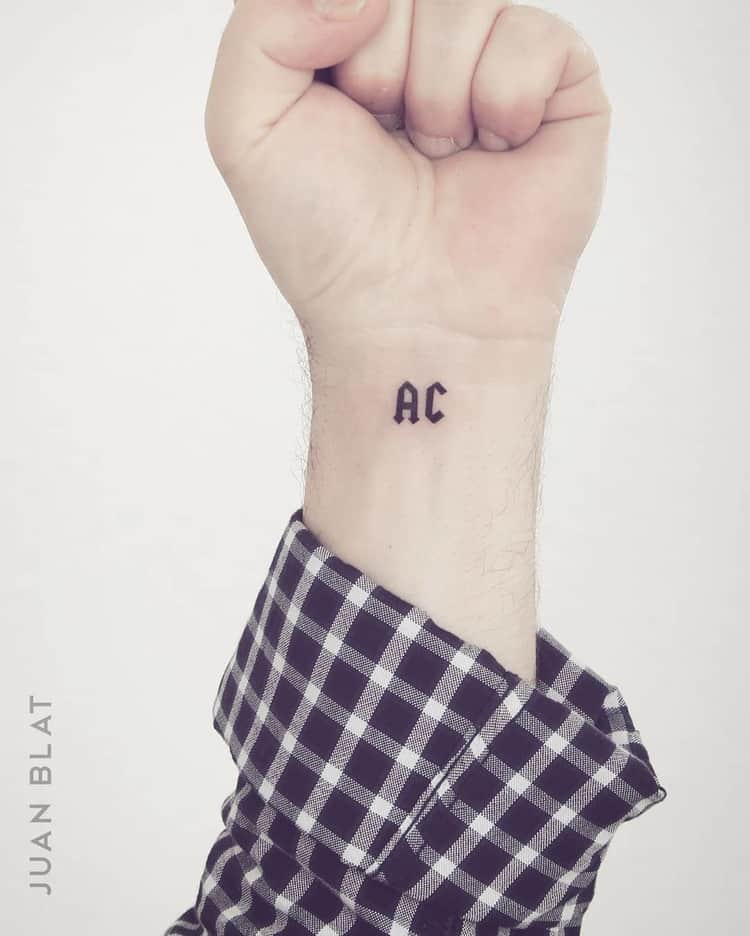 AC micro tattoo on wrist