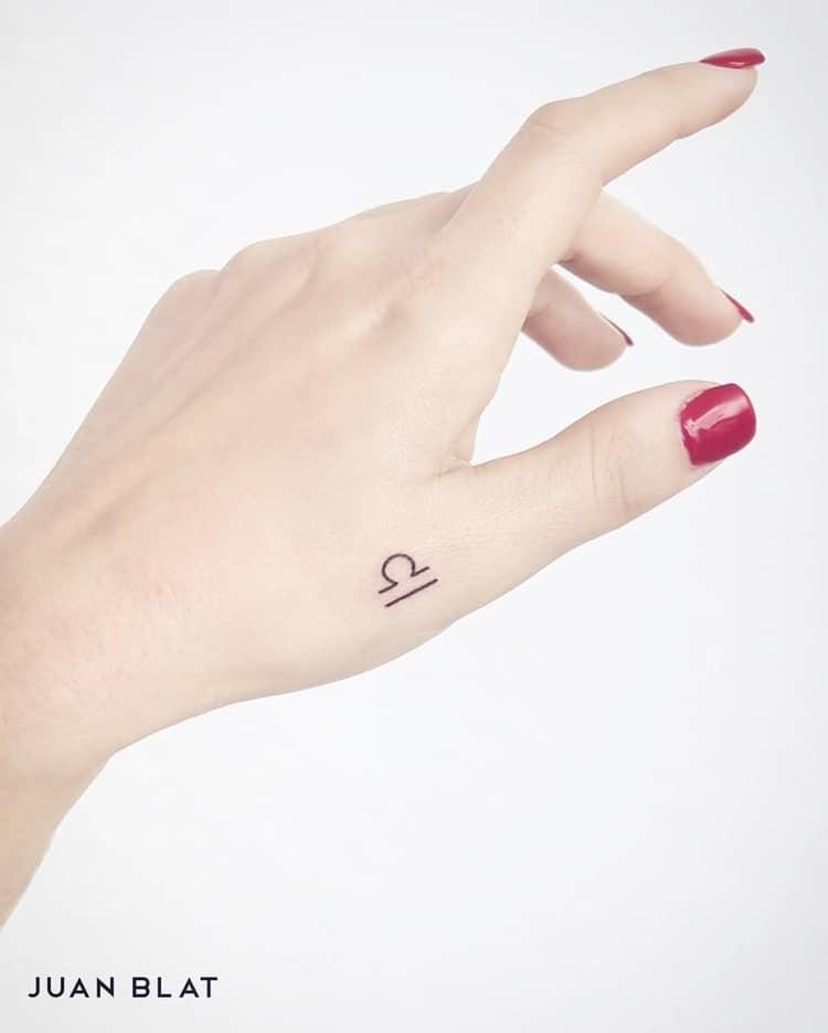 Libra micro-tattoo on hand