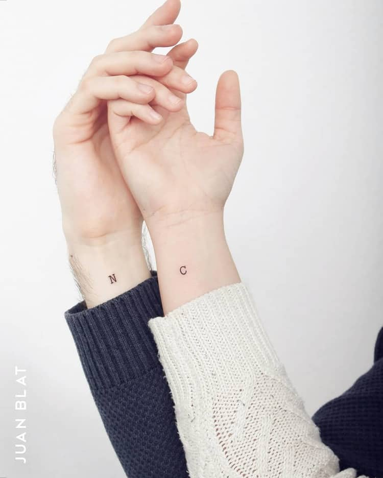 Micro initials tattoo on wrist